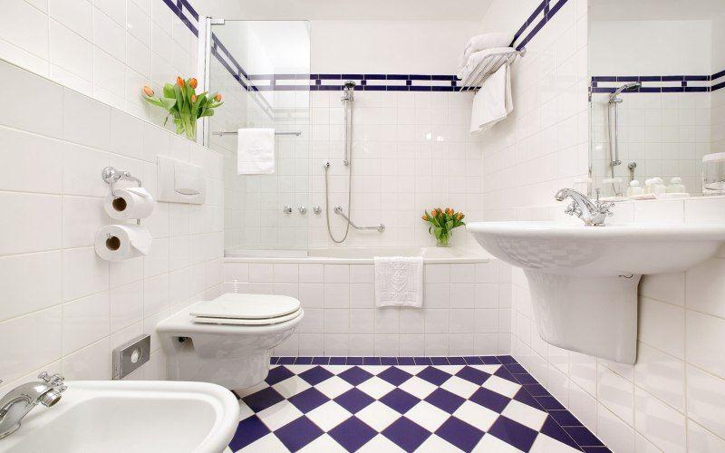 Пример графичной плитки на пол и белой ванны, фото