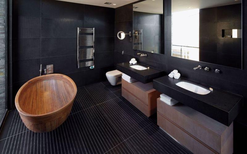 Черная ванная комната с акцентом на ванне и мебели